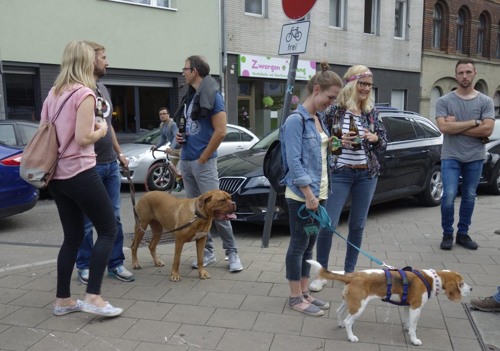 Participants of a walking tour are standing on a street with two dogs on leashes. Some of the participants are holding beers in their hands.