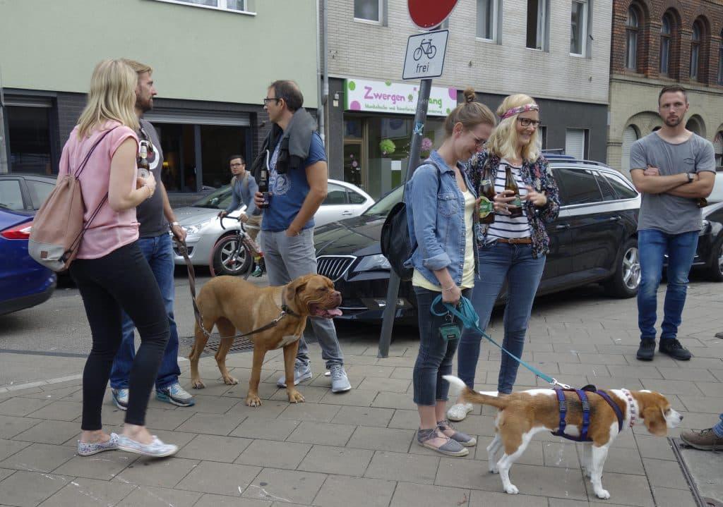 Gäste einer Stadtführung und ihre Hunde stehen auf einer Straße.