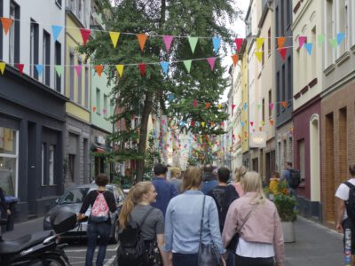 A group of people walks through a neighbourhood in Cologne. The street is very colourful.