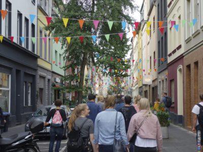 Un grupo de personas camina por uno de los barrios de Colonia. La calle es muy colorida.